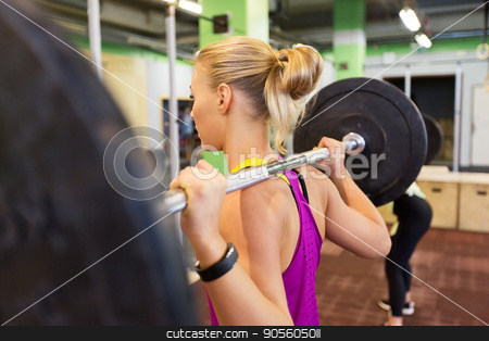 woman with barbell at group training in gym stock photo, fitness, sport and people concept - woman with barbell at group training in gym by Syda Productions