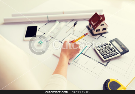 close up of hand on blueprint writing to notebook stock photo, business, architecture, building, construction and people concept - close up of architect hand with blueprint and architectural tools writing to notebook by Syda Productions
