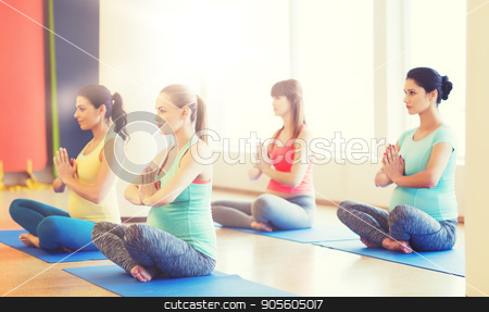 happy pregnant women exercising yoga in gym stock photo, pregnancy, sport, fitness, people and healthy lifestyle concept - group of happy pregnant women exercising yoga in lotus pose in gym by Syda Productions