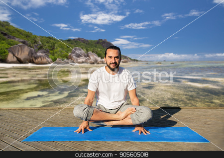 man making yoga in scale pose outdoors stock photo, fitness, sport, yoga, people and healthy lifestyle concept - man making scale pose lotus variation on mat over exotic tropical beach background by Syda Productions