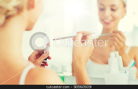 woman with lipstick and make up brush at bathroom stock photo, beauty, make up, cosmetics, morning and people concept - close up of smiling young woman with lipstick and make up brush at home bathroom mirror by Syda Productions