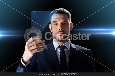businessman working with transparent tablet pc stock photo, business, augmented reality and future technology concept - businessman in suit working with transparent tablet pc computer over black background by Syda Productions
