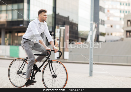 man with headphones riding bicycle on city street stock photo, lifestyle, transport and people concept - young man with headphones riding bicycle on city street by Syda Productions