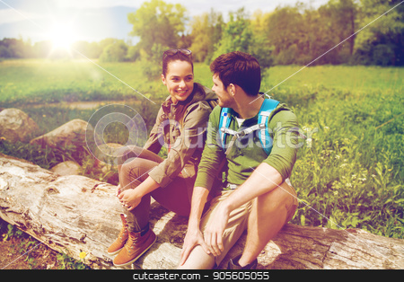 smiling couple with backpacks in nature stock photo, travel, hiking, backpacking, tourism and people concept - smiling couple with backpacks resting and talking in nature by Syda Productions