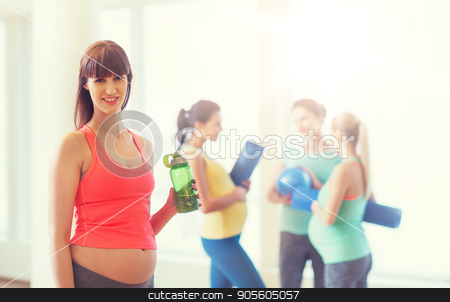 happy pregnant woman with water bottle in gym stock photo, pregnancy, sport, fitness, people and healthy lifestyle concept - happy pregnant woman with water bottle in gym by Syda Productions