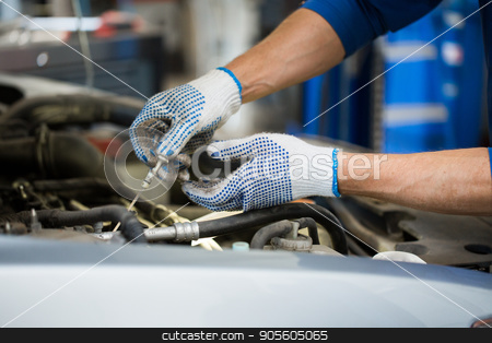 mechanic with dipstick checking motor oil level stock photo, car service, repair, maintenance and people concept - auto mechanic man with dipstick and lamp checking for motor oil level at workshop by Syda Productions