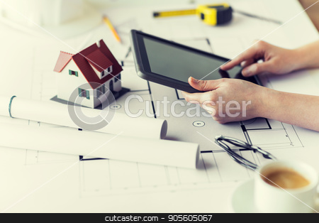 close up of hand with blueprint and tablet pc stock photo, business, architecture, building, construction and people concept - close up of architect hand with living house blueprint and tablet pc computer by Syda Productions