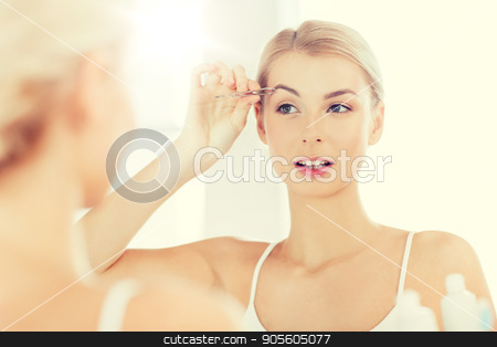 woman with tweezers tweezing eyebrow at bathroom stock photo, beauty and people concept - smiling young woman with tweezers tweezing eyebrow and looking to mirror at home bathroom by Syda Productions