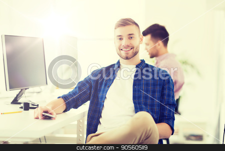 happy creative man with cellphone at office stock photo, business, technology, communication and people concept - happy young creative man or student with computer and smartphone at office by Syda Productions