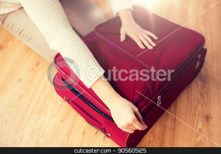 close up of woman packing travel bag for vacation stock photo, summer vacation, travel, tourism and objects concept - close up of woman packing and zipping travel bag for vacation by Syda Productions