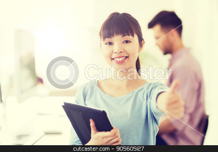 happy creative female office worker with tablet pc stock photo, business, startup and people concept - happy asian businesswoman or creative female office worker with tablet pc computer showing thumbs up by Syda Productions