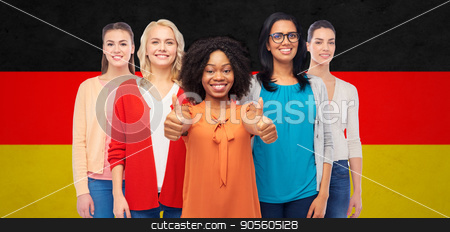 international german women showing thumbs up stock photo, diversity, ethnicity and people concept - international group of happy smiling different women showing thumbs up over german flag background by Syda Productions