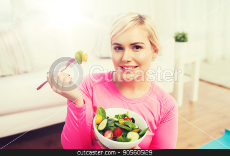 smiling young woman eating salad at home stock photo, healthy eating, dieting and people concept - smiling young woman eating vegetable salad at home by Syda Productions