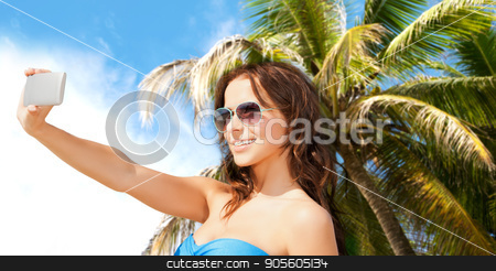 woman in swimsuit taking selfie with smatphone stock photo, technology, summer holidays, travel and people concept - happy young woman in bikini swimsuit and sunglasses taking selfie with smatphone over sky and palm trees background by Syda Productions