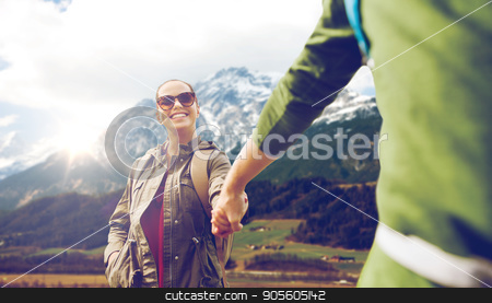 happy couple with backpacks hiking outdoors stock photo, travel, tourism and people concept - happy couple with backpacks holding hands over mountains background by Syda Productions