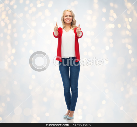 happy smiling young woman showing thumbs up stock photo, gesture, fashion and people concept - happy smiling young woman in red cardigan showing thumbs up over holidays lights background by Syda Productions