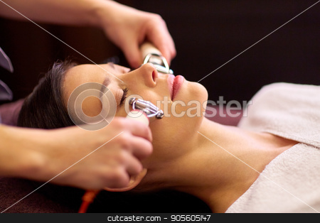 woman having hydradermie facial treatment in spa stock photo, people, beauty, cosmetology and technology concept - beautiful young woman having needle free mesotherapy or hydradermie facial treatment by microcurrent firming device in spa by Syda Productions