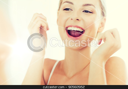 woman with dental floss cleaning teeth at bathroom stock photo, health care, dental hygiene, people and beauty concept - smiling young woman with floss cleaning teeth and looking to mirror at home bathroom by Syda Productions