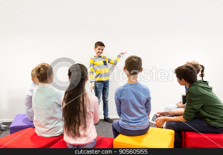 happy student boy showing something at white wall stock photo, education, elementary school, learning and people concept - happy student boy showing something at white wall by Syda Productions