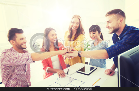 creative team holding hands together  at office stock photo, business, startup, architecture, gesture and people concept - happy international creative architect team or students with blueprint putting hands on top together at office by Syda Productions