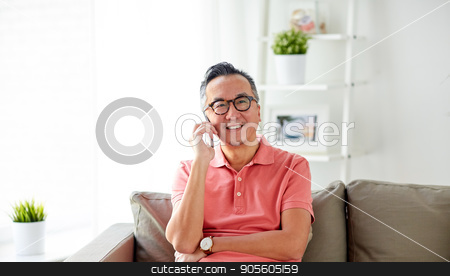 happy man calling on smartphone at home stock photo, technology, people, lifestyle and communication concept - happy man sitting on sofa calling on smartphone at home by Syda Productions