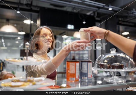 happy woman taking coffee cup from seller at cafe stock photo, small business, people and service concept - happy woman taking coffee cup from seller at vegan cafe by Syda Productions