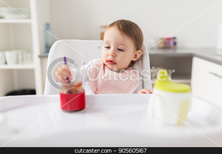 baby girl with spoon eating puree from jar at home stock photo, food, child, feeding and people concept - little baby girl with spoon sitting in highchair and eating puree from jar at home kitchen by Syda Productions