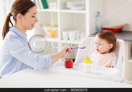 happy mother feeding baby with puree at home stock photo, family, food, eating and people concept - happy mother with puree and spoon feeding little baby sitting in highchair at home by Syda Productions