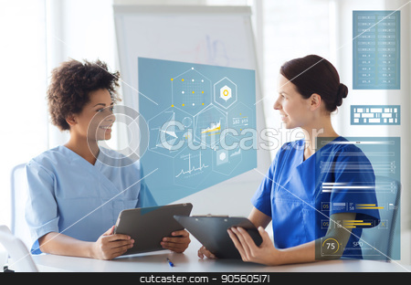 doctors with tablet pc and clipboard at hospital stock photo, medicine, healthcare, technology and people concept - happy female doctors with tablet pc computer and clipboard meeting at medical office by Syda Productions