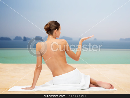 beautiful young woman in white towel with bare top stock photo, beauty, people and bodycare concept - beautiful young woman in white towel with bare top holding something invisible over infinity edge pool background by Syda Productions