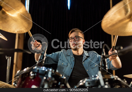male musician playing drums and cymbals at concert stock photo, music, people, musical instruments and entertainment concept - male musician with drumsticks playing drums and cymbals at concert or studio by Syda Productions