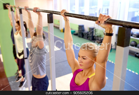 group of people hanging at horizontal bar in gym stock photo, sport, fitness, exercising and people concept - woman with heart-rate tracker hanging on horizontal bar at group training in gym by Syda Productions