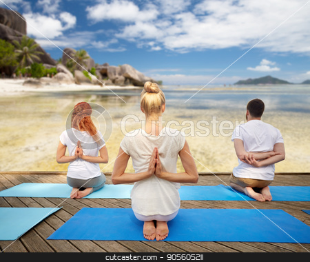 group of people making yoga exercises over beach stock photo, fitness, sport, yoga and healthy lifestyle concept - group of people exercising in reverse prayer pose over tropical beach background by Syda Productions
