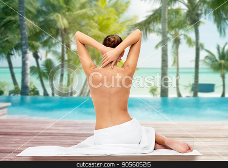 beautiful woman in towel with bare top on beach stock photo, beauty, people and bodycare concept - beautiful young woman in white towel with bare top over beach and outdoor swimming pool background by Syda Productions