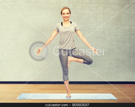 woman making yoga in tree pose on mat stock photo, fitness, sport, people and healthy lifestyle concept - woman making yoga in tree pose on mat over gym room background by Syda Productions