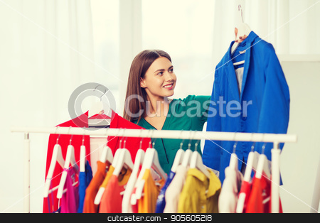 happy woman choosing clothes at home wardrobe stock photo, clothing, fashion, style and people concept - happy woman choosing clothes at home wardrobe by Syda Productions