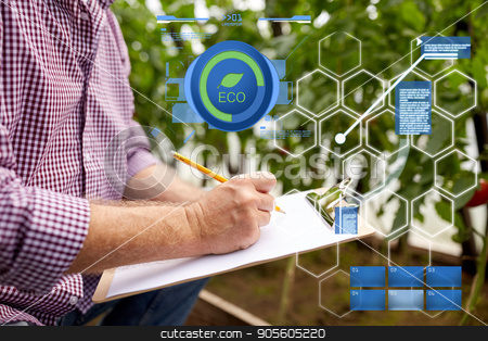 senior man writing to clipboard at farm greenhouse stock photo, organic farming, agriculture and people concept - senior man writing to clipboard at farm greenhouse by Syda Productions