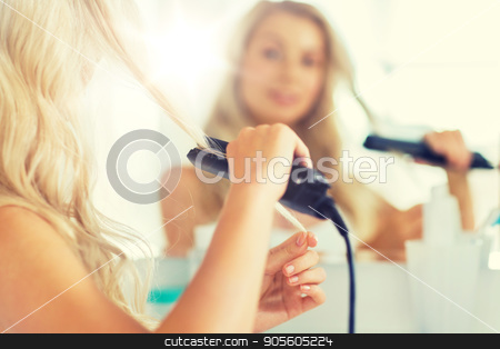 woman with styling iron straightening hair at home stock photo, beauty, hairstyle, morning and people concept - close up of young woman with styling iron straightening her hair and looking to mirror at home bathroom by Syda Productions