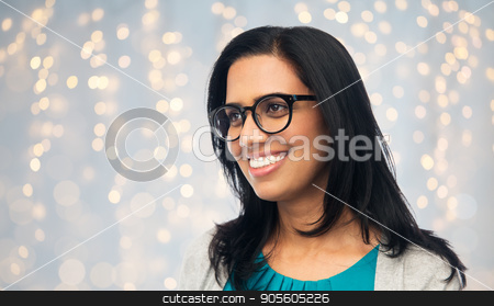 happy smiling young indian woman in glasses stock photo, vision, portrait and people concept - happy smiling young indian woman in glasses over holidays lights background by Syda Productions