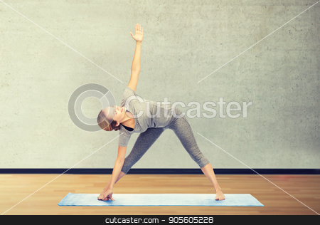 woman making yoga triangle pose on mat stock photo, fitness, sport, people and healthy lifestyle concept - woman making yoga triangle pose on mat over gym room background by Syda Productions