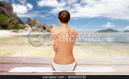 beautiful woman with bare top on beach stock photo, beauty, people and bodycare concept - beautiful topless young woman in white panties sitting on towel from back over exotic beach background by Syda Productions
