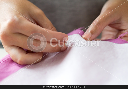woman with pins stitching paper pattern to fabric stock photo, people, needlework and tailoring concept - tailor woman with pins stitching paper pattern to fabric at sewing studio by Syda Productions