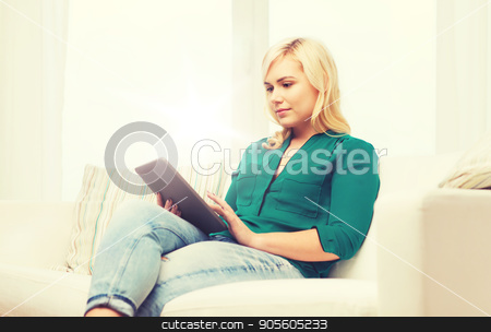 smiling woman with tablet pc at home stock photo, technology, internet and people concept concept - smiling woman sitting on couch with tablet pc computer at home by Syda Productions
