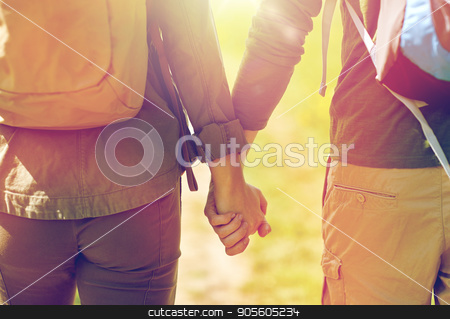 close up of couple with backpacks holding hands stock photo, travel, hiking, backpacking, tourism and people concept - close up of couple with backpacks holding hands and walking along country road by Syda Productions