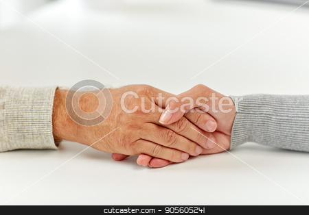 close up of old man and young woman holding hands stock photo, old age, support, charity, care and people concept - close up of senior man and young woman holding hands by Syda Productions