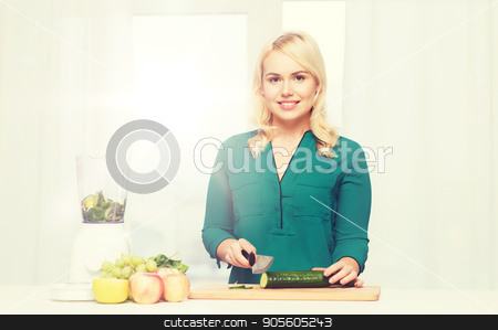 smiling woman with blender cooking food at home stock photo, healthy eating, cooking, vegetarian food, diet and people concept - smiling young woman with blender and knife chopping fruits and vegetables on cutting board at home by Syda Productions
