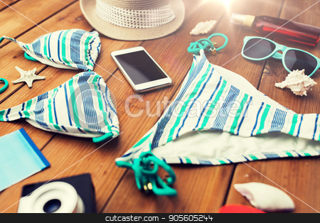 close up of smartphone and beach stuff stock photo, vacation, travel, tourism, technology and objects concept - close up of smartphone and beach stuff by Syda Productions