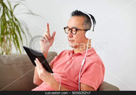 man with tablet pc and headphones at home stock photo, technology, people and lifestyle concept - happy man with tablet pc computer and headphones listening to music at home by Syda Productions
