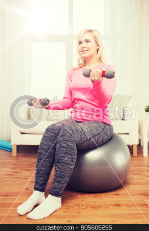 smiling woman with dumbbells exercising at home stock photo, fitness, sport, training and lifestyle concept - smiling woman with dumbbells and fit ball exercising at home by Syda Productions