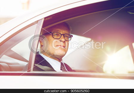 senior businessman driving on car back seat stock photo, transport, business trip and people concept - senior businessman driving on car back seat by Syda Productions